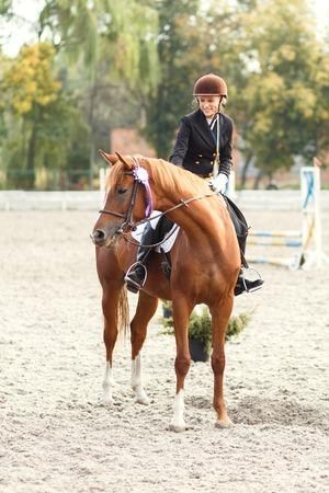 Adolescente jinete caballo ganador en concurso ecuestre. Deportista feliz joven con la medalla de primer lugar
