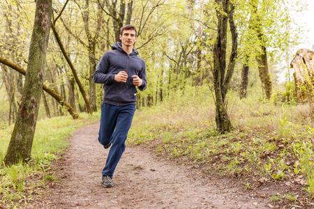 Jonge trail runner man joggen in de ochtend park. Sportman die in het bos loopt Stockfoto