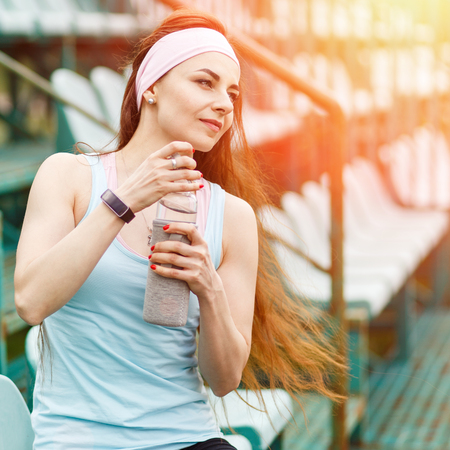 or thirsty: Young smiling woman with bottle of water after doing fitness workout. Pretty girl feeling thirsty after jogging