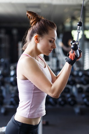Young slim woman doing pushdown on cable machine in gym. Athletic girl training triceps in fitness center