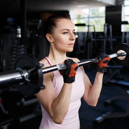 Jonge mooie vrouw doen biceps curl met EZ curl bar in een sportschool. Atletisch meisje training in een fitnesscentrum