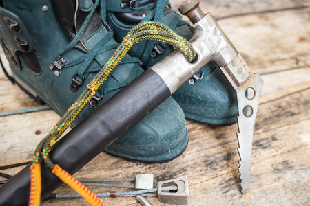 ice axe: Handmade ice axe with old worn mountain boots on wooden background
