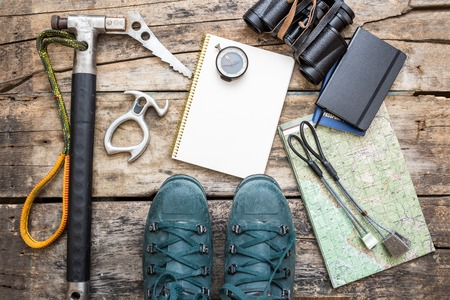 Climbing tools with boots and notebook on wooden background. Ice axe, nuts, compass, mountain boots and map lying on wood board