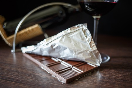 A chocolate bar in foil with glass of red wine on wooden table Stock Photo