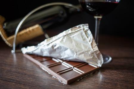 Een chocoladereep in folie met een glas rode wijn op houten tafel