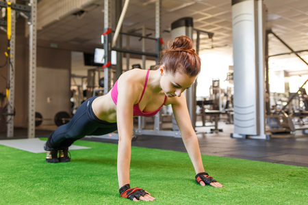 Young athletic woman doing core exercise in the gym. Crossfit fitness woman background