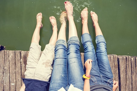 personas sentadas: Dos chicas y el muchacho se divierten en el muelle salpicando sus piernas en el agua del estanque. fondo de vacaciones de verano feliz