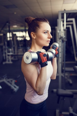 only the biceps: Young confident woman doing biceps curl exercise with dumbbells in fitness center. Slim girl training in the gym with dumbbells