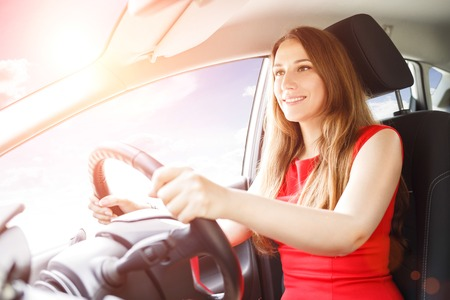 driving school: Young lady in red dress driving a car with sunbeams coming through the window. Driving school background Stock Photo