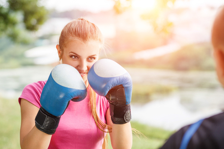 Young sporty woman training boxing with trainer at the park. Fitness outdoors workout