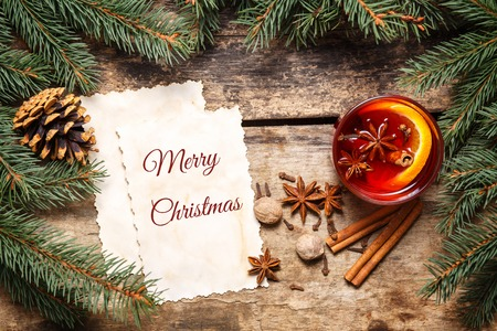 mulled wine spice: Merry Christmas card with mulled wine and decorative around on wooden background