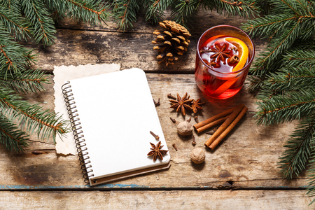 Blank notebook with mug of mulled wine on christmas decorative background Stock Photo