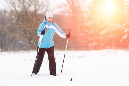 冬の公園で若い女性のクロスカントリーのスキー.
