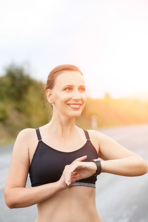 Young smiling fitness woman using her smart watch for heartrate after jogging. Healthy caucasian girl with fitness tracker watch Stock Photo