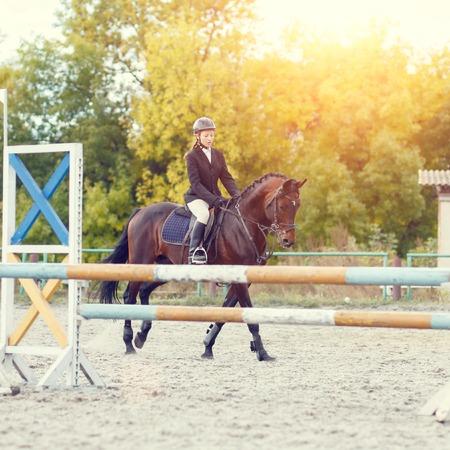 Deportista joven jinete del caballo en la competición deporte ecuestre. Fondo del acontecimiento deportivo. color cálido en tonos de imagen