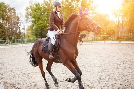 Young rider girl on horse on show jumping competition