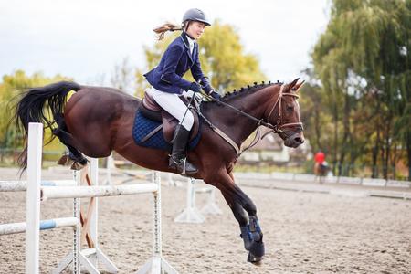 Deportista joven jinete del caballo en la competición deporte ecuestre. Fondo del acontecimiento de deporte