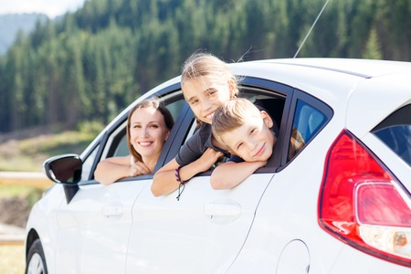 Happy young woman and her children sitting in a car and look out from windows. Family travel background image Stock Photo
