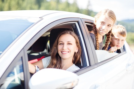 road of love: Happy young woman and her children sitting in a car and look out from windows. Family travel background image Stock Photo