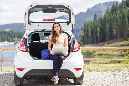 tronco: Mujer joven que usa su ordenador portátil sentado en el maletero del coche. Mujer de negocios que viajan de vacaciones en las montañas