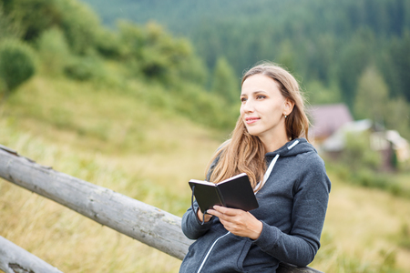 Young woman making notes into the notebook standing outdoors photo