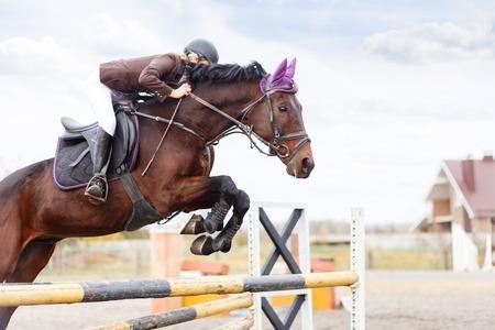 Young rider meisje bij jumping. Ruiter van het paard springt over hindernis