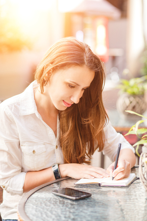 Young woman writing down into her notebook sitting at the table in restaurant photo