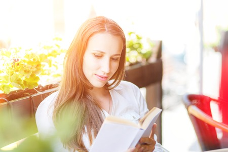 Young woman with long hair reading book at the table in cafe. Pretty caucasian girl with book at the summer terrace photo