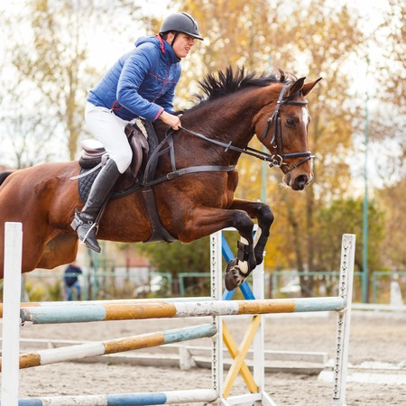 Young horseman on show jumping competition. Rider with sorrel horse jump over the hurdle