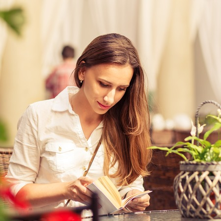 Young woman with long hair reading book at the table in cafe. Pretty caucasian girl with book at the summer terrace. Warm color toned image photo