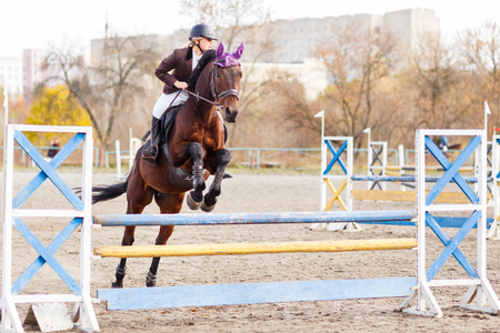 pace: Young female rider on bay horse jumping over hurdle on equestrian sport competition