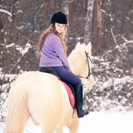 Young rider girl on albino horse in winter forest