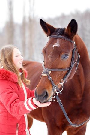 Teenage girl feeding bay horse on winter field