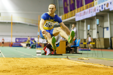 SUMY, UKRAINE - FEBRUARY 18, 2017: Serhiy Nykyforov performing his long jump in final on Ukrainian indoor track and field championship 2017 and win Editorial