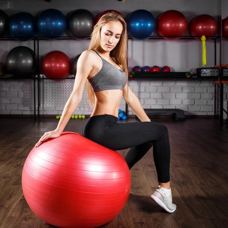 Jonge fitness meisje, zittend op de rode bal Stockfoto
