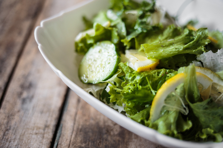 Fresh salad in white bowl on wooden background. Close up image of healthy food