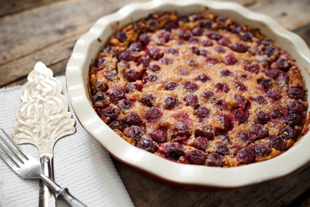 Cherry clafoutis pie in baking pan with spatula