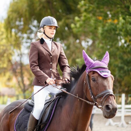 Young rider girl on horse at dressage competition Stock Photo - 77994077