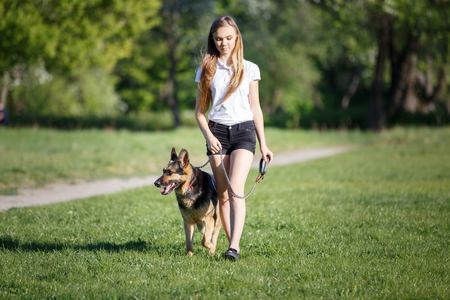 Teenage girl with her dog walking in park