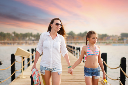Young woman with her daughter strolling along pier