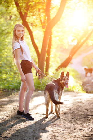 Teenage girl with her dog sitting in park