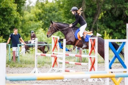 그녀의 트레이너와 함께 점프하는 젊은 라이더 소녀 훈련