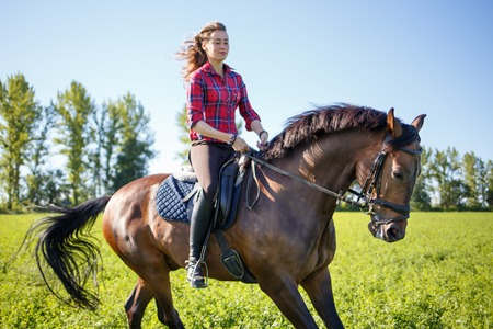 Happy young woman galloping horseback on field