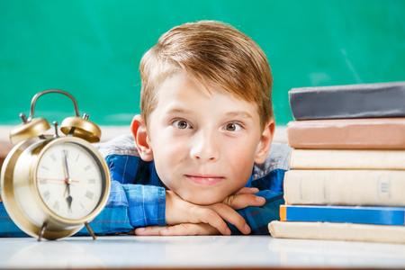 Small boy sitting with alarm clock near blackboard
