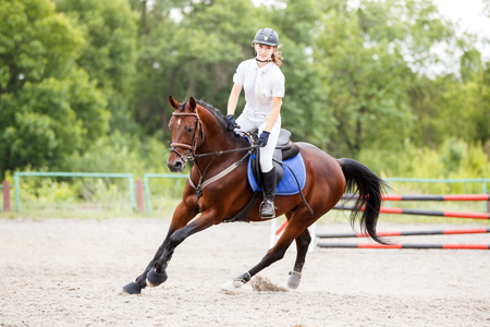 Young girl on horse at show jumping competition