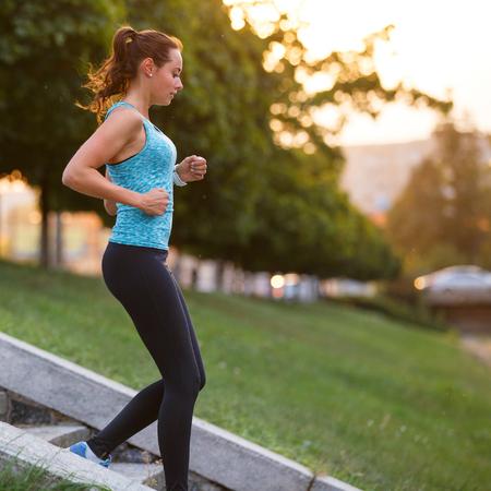 Jongelui die sportieve vrouw glimlachen die op treden dalen die in de ochtend opleiden. Geschiktheidsmeisje die treden gaan die in park aanstoten Stockfoto