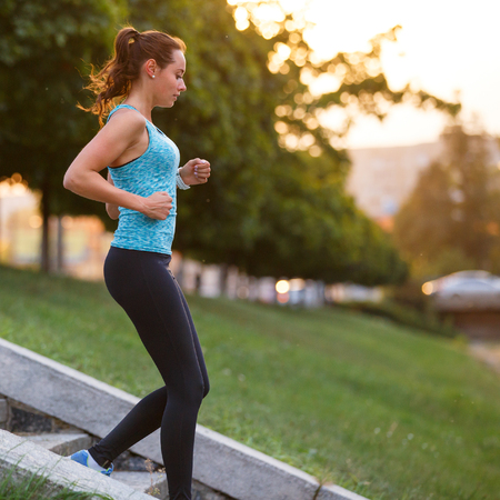 Joven sonriente mujer deportiva descendiendo en las escaleras de entrenamiento por la mañana. Chica de gimnasio bajando escaleras corriendo en el parque