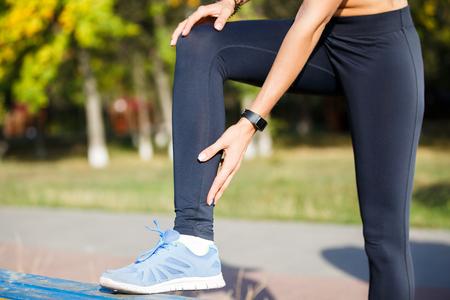 Kobieta biegacz dotykając ciasnych łydek podczas porannego joggingu. Tło koncepcja bólu lub urazu ścięgna Achillesa