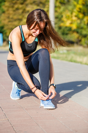 Young woman runner lacing up shoelaces on the trail jogging in park
