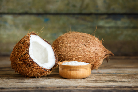 Fresh whole and cut in half coconuts with flakes on wooden background